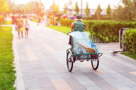 Photo for Urban street cleaner riding bicycle with garbage bag through municipal park on sunny day. Sweeper worker with bicycle on pavement at city street. - Royalty Free Image