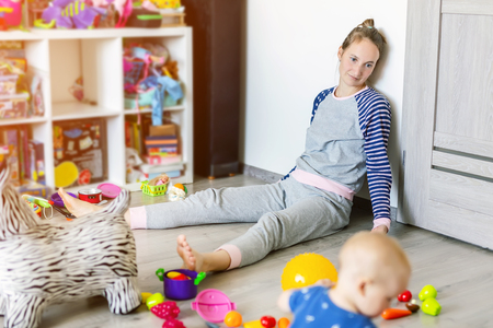 Foto de Tired of everyday household mother sitting on floor with hands on face. Kid playing in messy room. Scaterred toys and disorder. Happy parenting - Imagen libre de derechos