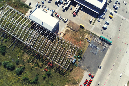 Photo pour Steel frame construction of modern storage warehouse building at big city suburb. Aerial drone view from above. - image libre de droit