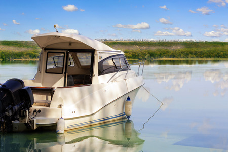 Foto de Big luxury fishing boat with cabin moored near river or lake shore in still water. Blue sky on the background. Summer adventure, relax and travel. Boat rental service. - Imagen libre de derechos