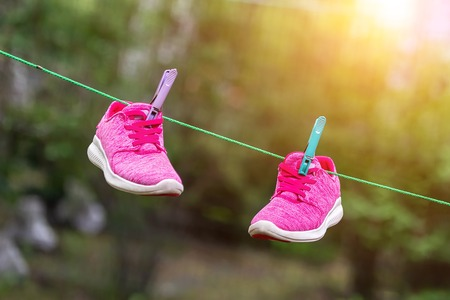 Photo for Pair of bright sport fitness sneakers hanged on clothespin at backyard after laundry outdoors. Preparartion for running training or marathon. - Royalty Free Image