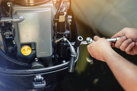 Photo pour mechanic repairing inflatable motorboat engine at boat garage. Ship engine seasonal service and maintenance. Vessel motor with open cover. - image libre de droit