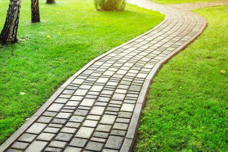 Photo for Slab stone paved path way along green grass lawn at park or backyard. Walkway footpath road at house yard garden. - Royalty Free Image