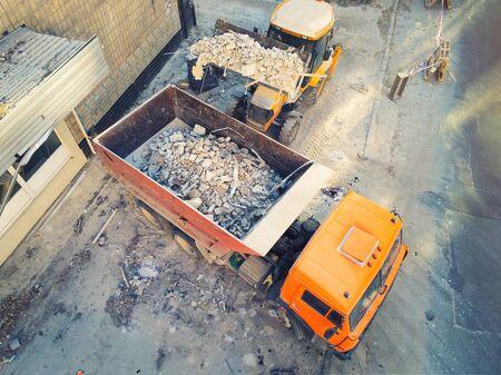 Photo pour Bulldozer loader uploading waste and debris into dump truck at construction site. building dismantling and construction waste disposal service. Aerial drone industrial background. - image libre de droit
