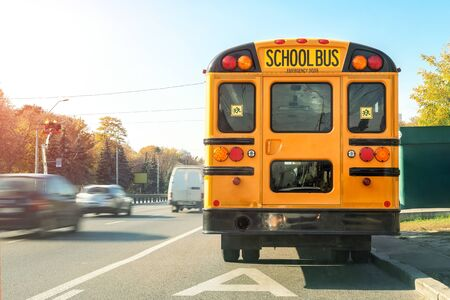 Photo pour Big classic vintage american yellow schoolbus standing on a bus lane at highway and waiting pupils and children for school trip road. School bus transport back door view on route bright morning time. - image libre de droit