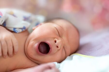 Photo pour One week newborn adorable innocent baby lying at baycot and funny yawning.Portrait of sleepy caucasian infant tired child on bed. Wide open mouth and closed eyes new born human kid - image libre de droit