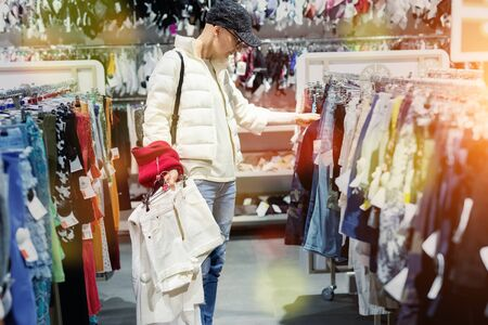 Foto per Young adult beautiful woman choosing clothes at market or retail clothing store in mall indoors. Sale discount season at fashion boutique. Casual modern comfortable wardrobe lifestyle. - Immagine Royalty Free