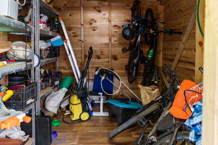 Photo pour Suburban home wooden storage utility unit shed with miscellaneous stuff on shelves, bikes, exercise machine, ladder, garden tools and equipment. Messy and chaos at house yard barn. Organization order - image libre de droit