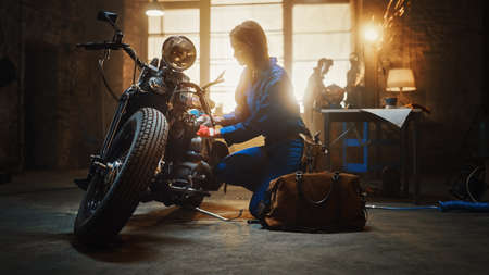 Photo for Young Beautiful Female Mechanic Comes Working on a Custom Motorcycle in Garage. Talented Girl Wearing a Blue Jumpsuit. She Uses a Ratchet to Tighten Nut Bolts. Creative Authentic Workshop. - Royalty Free Image