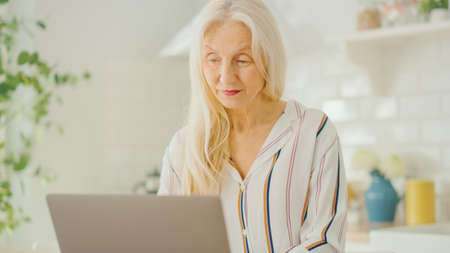 Photo for Beautiful Senior Woman Using Laptop Computer in a Sunny Kitchen. She Smiles. Grandmother is Connected with Children via internet and Social Media. Pensioner Working from Home. - Royalty Free Image