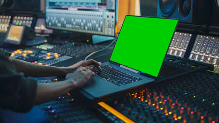 Photo pour Female Artist, Musician, Producer, Audio Engineer Working in Music Record Studio on a New Album, Use Green Screen Laptop Computer, Control Desk for Mixing and Creating Hit Song - image libre de droit
