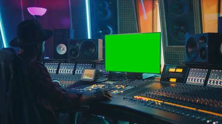 Photo pour Stylish Audio Engineer Producer Working in Music Record Studio, Uses Green Screen Chroma key Computer Display, Mixer Board Equalizer and Control Desk to Create New Hit Song. Black Artist Musician - image libre de droit