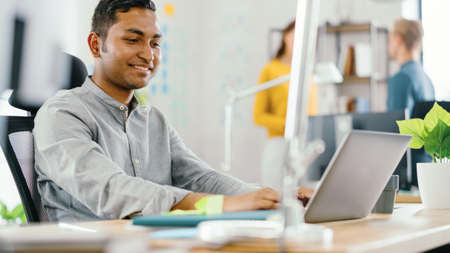 Photo for Handsome Smiling Indian Office Worker Sitting at His Desk works on a Laptop. In the Background Modern Office with Diverse Team of Young Professionals Working. - Royalty Free Image