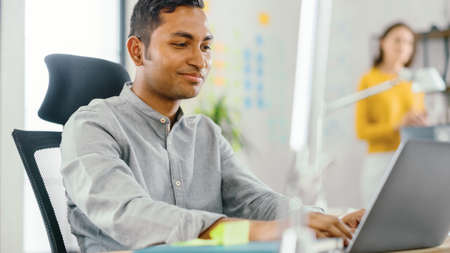 Photo pour Smart and Handsome Indian Office Worker Sitting at His Desk works on a Laptop. In the Background Modern Office with Diverse Team of Young Professionals Working. - image libre de droit