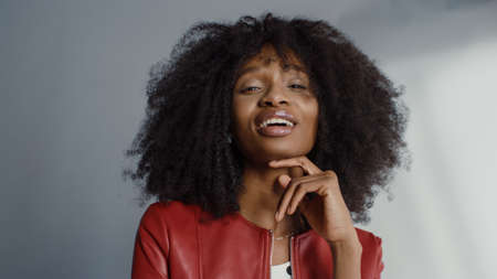 Foto de Attractive Black Girl with Lush Curly Hair Posing for a Fashion Magazine Photoshoot. Beautiful Girl Smiles Playfully and Acts for Photo Shoot Made in Professional Studio. Portrait Shot - Imagen libre de derechos