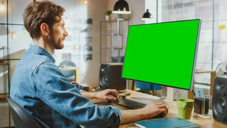 Photo pour Male Creative Designer with Beard and Jeans Shirt Works on His Personal Computer with Big Green Screen Mock Up Display. He Works in Cool Office Loft. - image libre de droit
