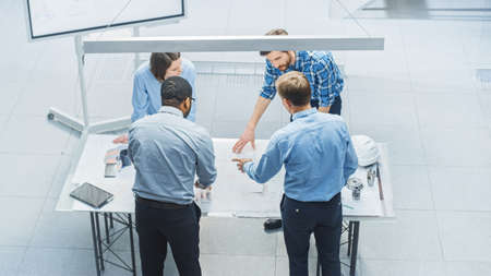 Photo for In Busy Engineering Facility: Diverse Group of Engineers, Technicians, Specialists Working on Design for Industrial Engine Prototype. Professionals Talk, Work with Drawings, Use Computers. High Angle - Royalty Free Image