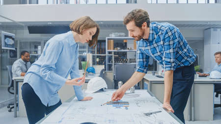 Photo pour In the Industrial Engineering Facility: Young Female Designer Works with Chief Industrial Engineer, They have Discussion, Analyse and Correct Engine Design Technical Drafts that are Lying on the Table - image libre de droit