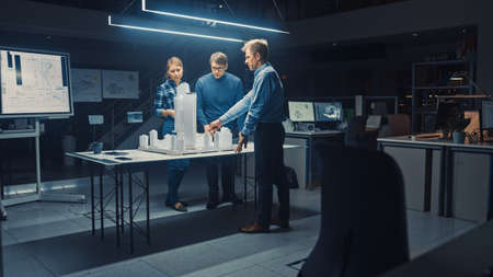 In the Creative Architectural Agency Two Professional Designers Talk with Chief Project Engineer, They Work on a Model of a City District. Urban Planners Work on a Functional Building Model.