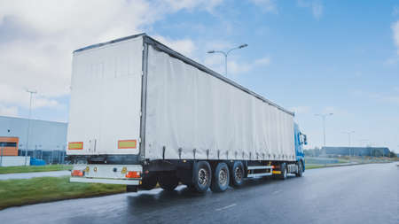 Photo for Long Haul Semi-Truck with Cargo Trailer Full of Goods Travels on the Highway Road. Daytime Driving Across Continent Through Rain, Fog. Industrial Warehouses Area. - Royalty Free Image