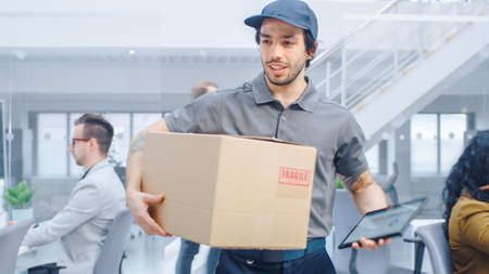 Happy Delivery Man Wals in Corporate Office with Tablet Computer and Delivers Cardboard Package to a Worker. Big Bright Modern Business Company Office with Professional Businesspeople Working