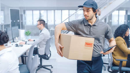 Happy Delivery Man Walks in Corporate Office with Tablet Computer and Delivers Cardboard Package to a Worker. Big Bright Modern Business Company Office with Professional Businesspeople Working