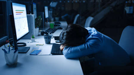 Photo pour In the Office at Night Overworked Tired Office Worker Uses Desktop Computer but Falls Asleep Fast. Tired Exhausted Businessman Falls asleep at His Job - image libre de droit