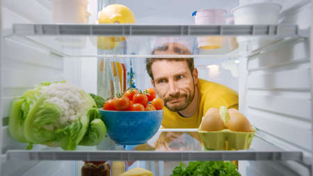 Inside Kitchen Fridge: Young Disappointed Man Looks inside the Fridge. Man Found Nothing for His Snack Time. Point of View POV Shot from Refrigerator full of Healthy Food