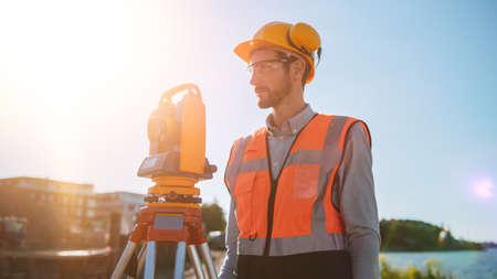 Photo pour Construction Worker Using Theodolite Surveying Optical Instrument for Measuring Angles in Horizontal and Vertical Planes on Construction Site. Worker in Hard Hat Making Projections for the Building. - image libre de droit