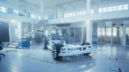 Photo pour Concept of Authentic Electric Car Platform Chassis Prototype Standing in High Tech Industrial Machinery Design Laboratory. Hybrid Frame include Tires, Suspension, Engine and Battery. - image libre de droit