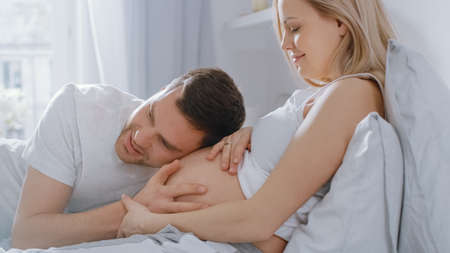 Photo for Happy Young Couple Cuddling Together in the Bed, Young Woman is Pregnant, Loving Partner Leans and Listens to a Baby Moving and its Heartbeat in the Belly. Tender and Loving Moments of Family Life. - Royalty Free Image