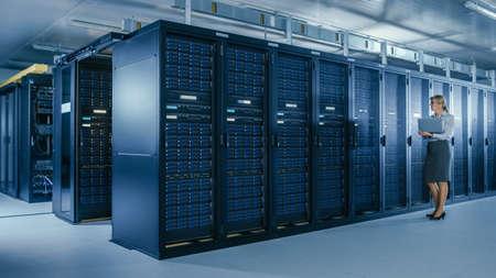 Photo pour In Data Center: Female IT Specialist Walks along the Row of Operational Server Racks, Uses Laptop to Run Maintenance Programme. Modern High-Tech Telecommunications Operational Data Center. - image libre de droit