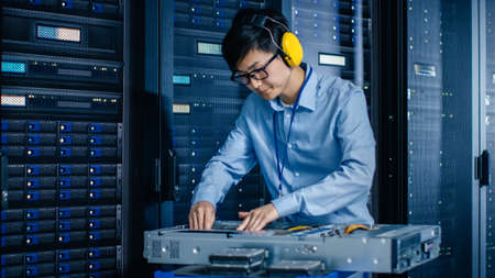 Photo pour In the Modern Data Center: IT Engineer Wearing Protective Muffs Installs New Hardware for Server Rack. IT Specialist Doing Maintenance, Updating Hardware for Stable Functioning of Database System. - image libre de droit