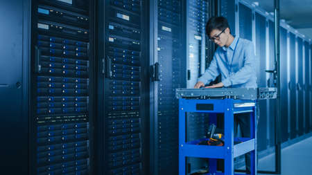 Photo pour In the Modern Data Center: IT Technician Working with Server Racks, on a Pushcart Various Equipment Needed for Installing New Hard Drives, Doing Hardware Maintenance and Diagnostics. - image libre de droit