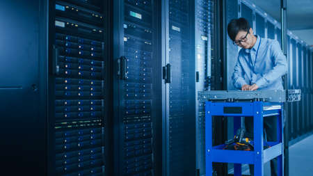Photo pour In the Modern Data Center: IT Technician Working with Server Racks, on a Pushcart Installing New Hardware. Engineer Doing Maintenance and Diagnostics of the Database. - image libre de droit