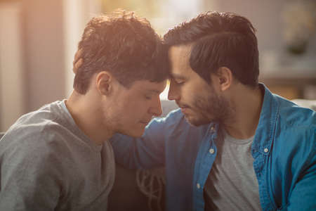 Photo for Cute Male Queer Couple Put Their Heads Together and Close Their Eyes. Sweet Gentle Loving Gay Relationship Moment. Room Has Modern Interior. Shot with Rainbow Flare Effect. - Royalty Free Image