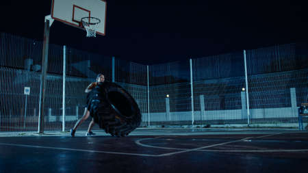 Foto de Beautiful Energetic Fitness Girl is Doing Exercises in a Fenced Outdoor Basketball Court. Shes Flipping a Big Heavy Tire in a Foggy Night After Rain in a Residential Neighborhood Area. - Imagen libre de derechos