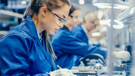 Photo pour Female Electronics Factory Workers in Blue Work Coat and Protective Glasses Assembling Printed Circuit Boards for Smartphones with Tweezers. High Tech Factory with more Employees in the Background. - image libre de droit