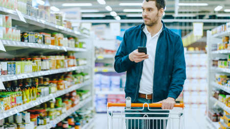 Foto für At the Supermarket: Handsome Man Uses Smartphone and Looks at Nutritional Value of the Canned Goods. Hes Standing with Shopping Cart in Canned Goods Section. - Lizenzfreies Bild