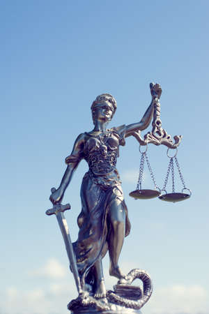 image of themis sculpture, femida or justice goddess on bright blue sky sunny outdoors background