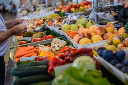 Photo pour Picture of grocery stall with various fresh fruits and vegetables and man making purchases. - image libre de droit