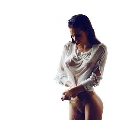 Beautiful sexy girl in wet shirt isolated in whiteの写真素材