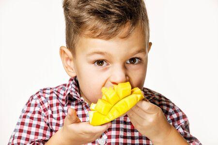 Photo for handsome boy in a red shirt is eating a mango - Royalty Free Image