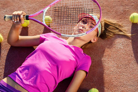 Top view of cute girl in the cap lying on tennis outdoor court with racket in the hand and a lot of balls on the ground after training.