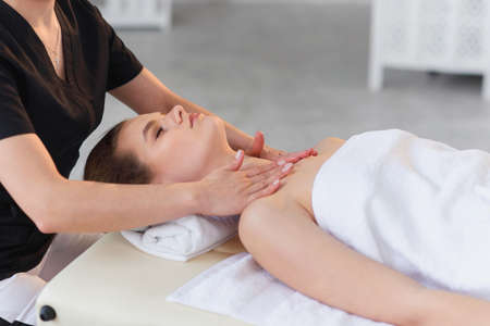Photo pour Happy young woman having massage while lying on the massage table in the spa salon. - image libre de droit
