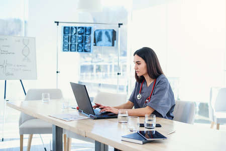 Photo pour Young female doctor works with laptop in the conference room at hospital. Professional doctor in medical uniform examines patients analysis. - image libre de droit