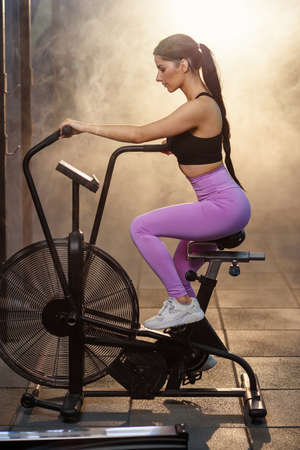 Photo pour Fit attractive woman working out on the exercise bike at the gym. - image libre de droit