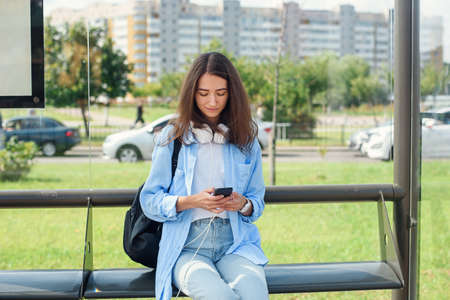 Photo pour Charming girl with trendy look use smart phone while waiting on bus stop. Woman holds mobile phone while sitting on a public station and waiting for taxi. - image libre de droit