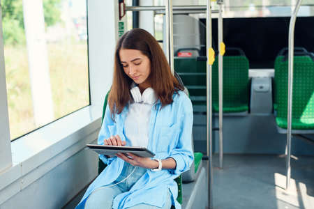 Photo for Happy woman reading a Tablet or ebook in a train station while is waiting for public transport - Royalty Free Image