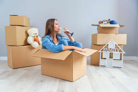 Photo for Happy woman drinks champagne from a glass while sitting inside a cardboard box in new apartment. - Royalty Free Image